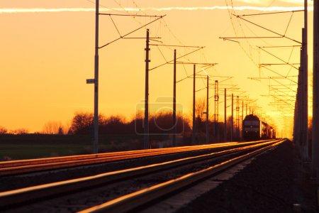 Photo pour Train fret dans le chemin de fer à un coucher de soleil - image libre de droit