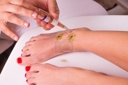 Photo for Glitter tattoo on a caucasian woman's leg. - Royalty Free Image