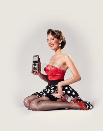 Photo pour Pin-up girl détient le vieil appareil photo argentique de tlr de 1950 - image libre de droit
