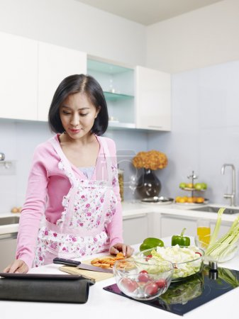 Photo for Asian housewife looking at tablet computer while preparing meal. - Royalty Free Image