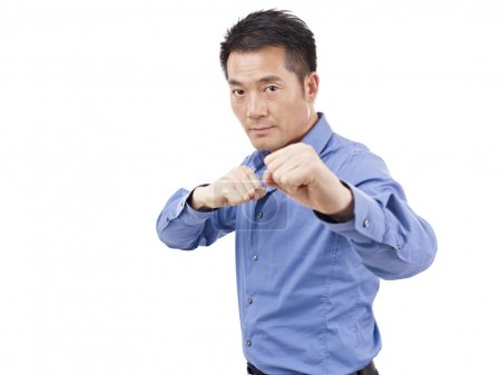 Asian businessman showing karate move