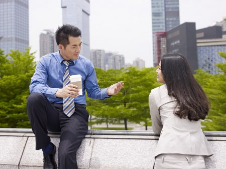 Photo for Asian businessman and businesswoman talking outdoors. - Royalty Free Image