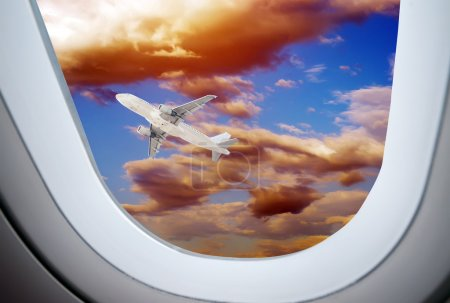 Through the aircraft windows, Airliner against the setting sun.