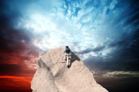 Photo for Young man climbing on a limestone wall with blue sky on the background - Royalty Free Image