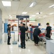 Airport security check with passenger walking thro...