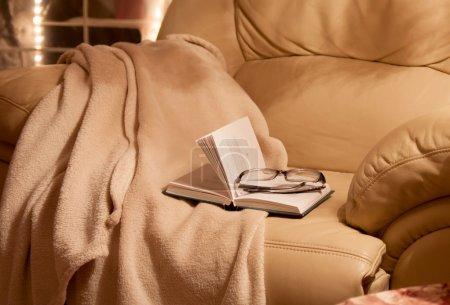 Photo pour Intérieur de la maison. Une chaise confortable avec une couverture, un livre et un café - image libre de droit
