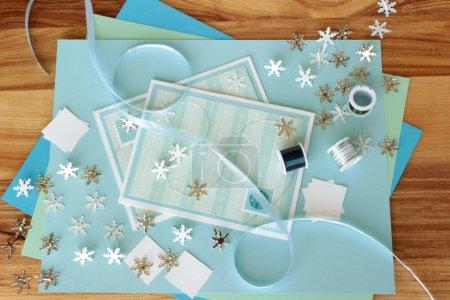 Photo pour Une image de deux cartes de vœux faites à la main avec un thème d'hiver, avec des fournitures de fabrication de cartes, y compris des plaquettes en forme de flocon de neige et du fil d'artisanat . - image libre de droit
