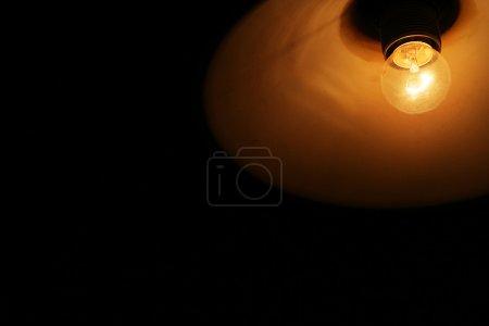 Photo pour Ampoule avec abat-jour sur fond noir. Photo qualitative avec copyspace est bon pour le concept de lumière, électricité, énergie, éclairage, idée, innovation, etc. - image libre de droit