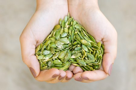 Photo for Pumpkin seeds' kernel in woman hands forming heart shape - Royalty Free Image