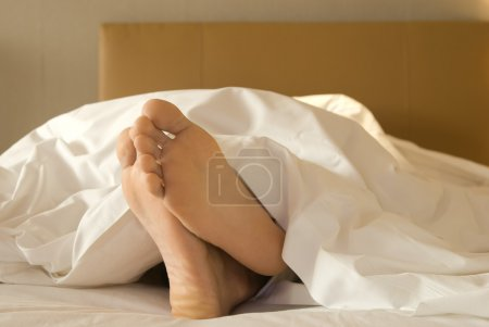 Feet of a man lying down on bed