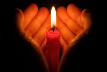 Photo for Hands holding a burning candle in dark - Royalty Free Image