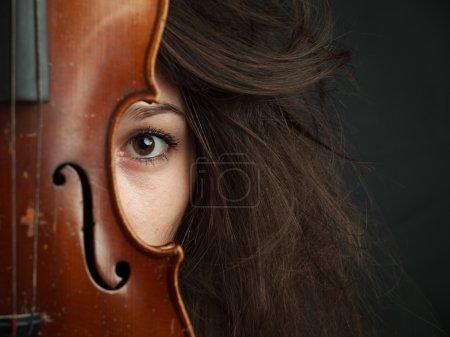 Photo pour Jeune fille brune avec le violon en chambre noire. belle adolescente européen. instruments de musique. femme au violon. fille en studio. - image libre de droit