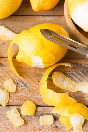 Photo pour Peeling citrons sur table en bois. faible profondeur de champ. - image libre de droit
