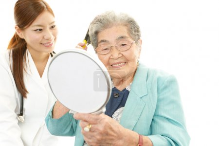 Smiling Asian doctor and senior woman
