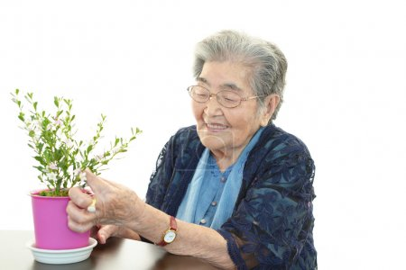 Smiling old woman with plant
