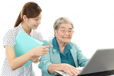 Young woman helping an elderly lady use a computer