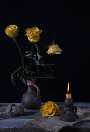 Still life with yellow withered flowers and candlestick with bur