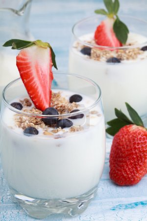Photo for Delicious and healthy yogurt with granola or muesli with nuts, raisins and berries (blueberries and strawberries) and jug with milk - Royalty Free Image
