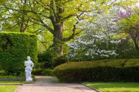 Photo for A section of a Cleveland city garden with statuary and flowering trees in spring - Royalty Free Image