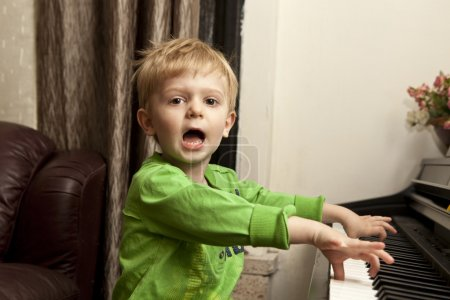 Boy playing on piano.