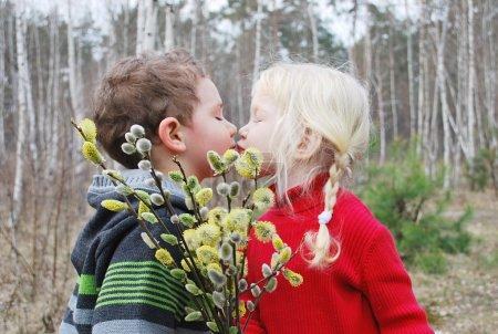 Spring. Boy kisses the girl and gives her a bouque...
