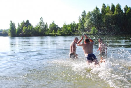 In the summer, the boys are swimming in the lake, diving, splash