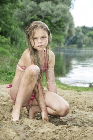 Photo pour Fille d'été avec des cheveux longs, assis sur la plage en maillot de bain sur le sable près du lac. - image libre de droit