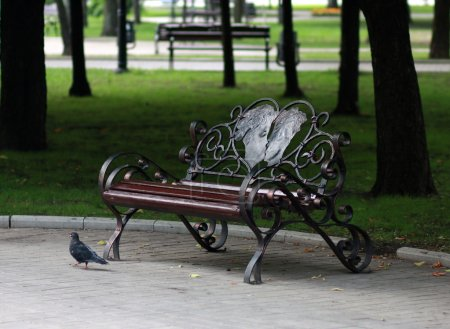 Metal forged bench in autumn park with a pair of lovers in heart