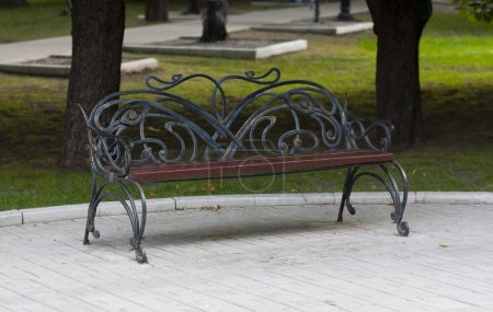 Metal forged bench in summer park