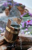 Dřevěné vědro za dobře s tekoucí vodou a pavučiny