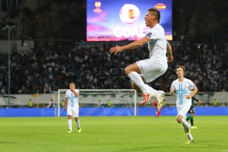 Soccer players celebrate a score