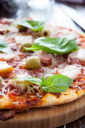 thin pizza with bacon, olives and basil on board
