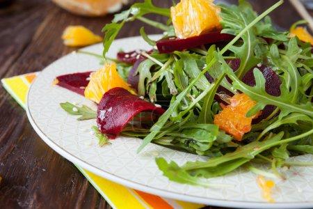 beet salad with arugula and slices of orange