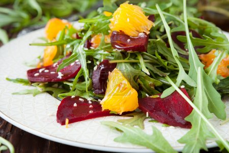 Photo for Beet salad with fresh arugula and slices of orange, food - Royalty Free Image