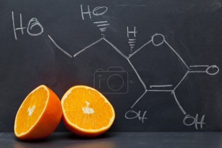 Photo for Structural formula of vitamin C on blackboard with orange - Royalty Free Image
