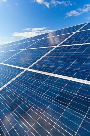 Foto de Campo de paneles de energía solar fotovoltaica para la producción de energía renovable con el azul del cielo y las nubes - Imagen libre de derechos