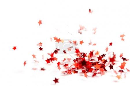 Photo pour Dispersés rouge petite étoiles brillant confettis volent sur fond blanc - image libre de droit