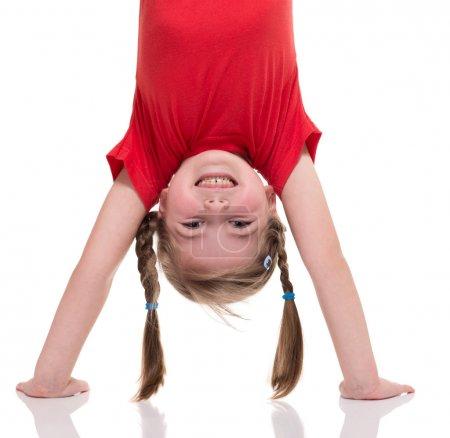 little girl standing on her hand