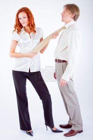 junge Frau zieht Mann an Krawatte