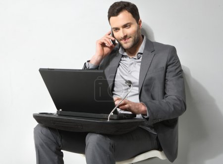 Young businessman talking on the phone and working on is laptop