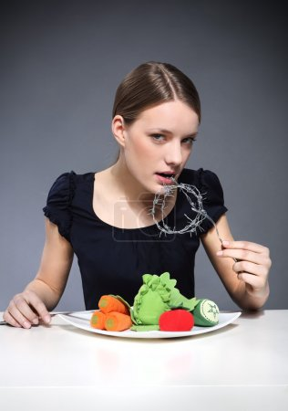 Photo for Young girl sitting over a plate of vegetables and put into the mouth barbed wire. - Royalty Free Image