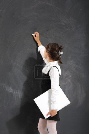 Photo pour Petite fille mignonne debout près d'une commission scolaire noire - image libre de droit