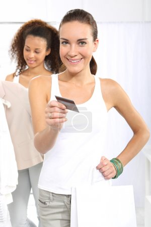 Photo for Woman in clothing store pay for purchases by credit card. Two women shopping in boutique clothing, mulatto and Caucasian - Royalty Free Image