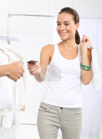 Photo for Woman in clothing store pay for purchases by credit card. - Royalty Free Image