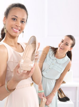 Shopping in a boutique, women buy shoes