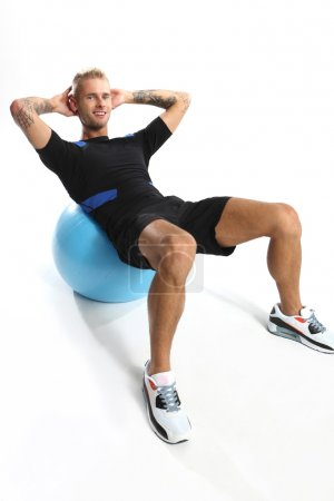 Photo pour Gymnastique, exercices de l'homme sur le ballon - image libre de droit