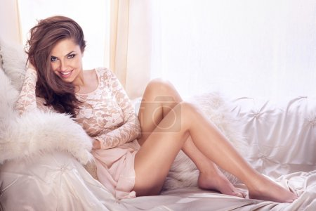 Photo for Fashion photo of beautiful young sexy woman wearing lace dress, relaxing and smiling in bright room, on the white couch. Looking at camera. - Royalty Free Image