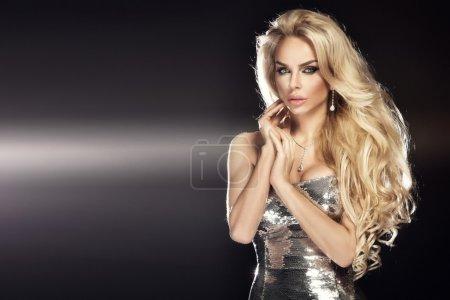 Photo pour Photo de mode de belle jeune femme blonde portant une robe argentée pailletée. Cheveux longs et bouclés . - image libre de droit