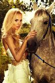 Portrét nádherná blondýnka s koněm