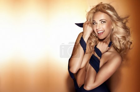 Happy beautiful blonde woman posing, looking at camera.
